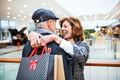 Happy senior couple with paper bags in shopping center, hugging. - PhotoDune Item for Sale