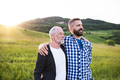 A portrait of an adult hipster son with senior father in nature at sunset, arms around each other. - PhotoDune Item for Sale