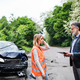 An insurance agent talking to a woman driver by the car on the road after an accident. - PhotoDune Item for Sale