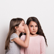 A small girl whispering something in an ear of her friend. - PhotoDune Item for Sale