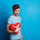 Portrait of a sad young man in a studio on a blue background, holding red heart. - PhotoDune Item for Sale