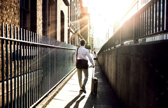 Rear view of businessman with suitcase walking up the street in London. - Stock Photo - Images