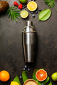 Cocktail shaker, tropical fruits and leaves on a dark background - PhotoDune Item for Sale