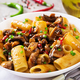 Vegetarian pasta  rigatoni with mushrooms and chilli peppers in white bowl on grey table.  - PhotoDune Item for Sale