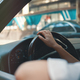 Close-up woman holding hand on steering wheel - PhotoDune Item for Sale