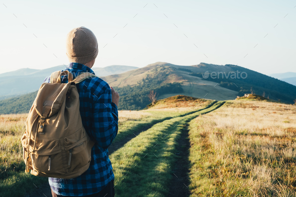 Man with backpack on mountains road - Stock Photo - Images