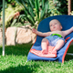 Baby boy lies on a deck-chair on green lawn - PhotoDune Item for Sale
