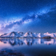 Milky Way over snow covered mountains and sea at night in winter - PhotoDune Item for Sale