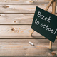 Blackboard with back to school text, dark wooden background, copy space - PhotoDune Item for Sale