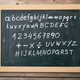 Letters and numbers on a blackboard with frame on wooden wall background - PhotoDune Item for Sale