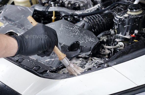 Car detailing  maintenance cleaning engine with the foam and a brush - Stock Photo - Images
