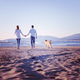 couple with dog having fun on beach on autmun day - PhotoDune Item for Sale