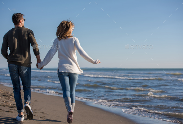 Loving young couple on a beach at autumn sunny day - Stock Photo - Images