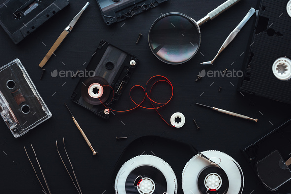 Flat lay audio and video cassette parts on dark background - Stock Photo - Images