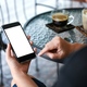 Hand holding smartphone with coffee on the table. - PhotoDune Item for Sale