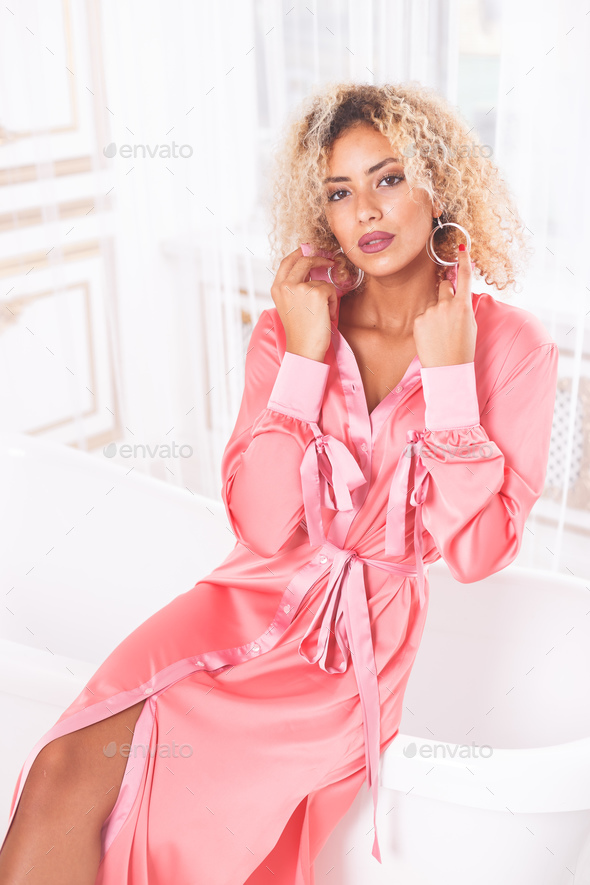Beautiful African woman wearing pink dress in bathroom - Stock Photo - Images