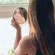 Young beautiful woman doing make-up in front of mirror - PhotoDune Item for Sale