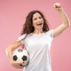 Fan sport woman player holding soccer ball isolated on pink background - PhotoDune Item for Sale