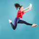 Image of young woman over pink background using laptop computer or tablet gadget while jumping. - PhotoDune Item for Sale