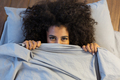 Beautiful black woman hiding behind blanket and smiling - PhotoDune Item for Sale
