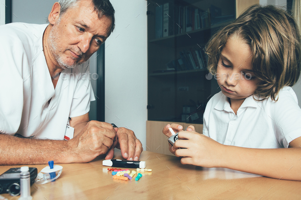 Doctor watches a diabetic child - Stock Photo - Images