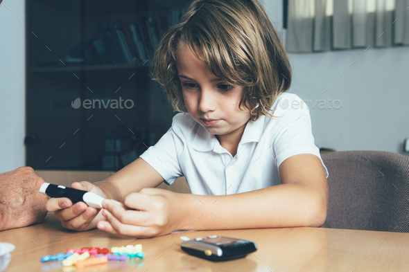 Diabetic child makes a lancing - Stock Photo - Images