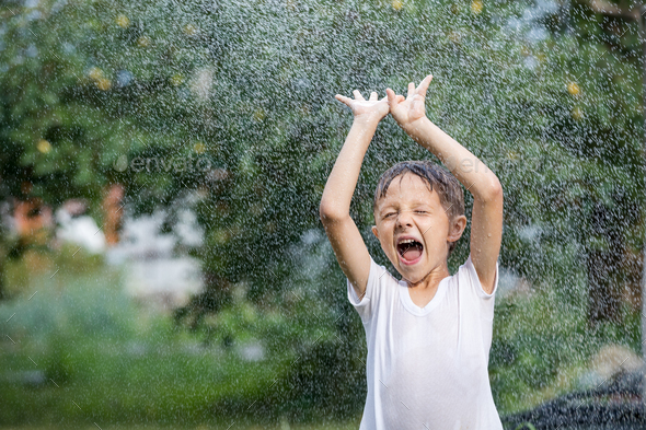 Happy little boy pouring water from a hose. - Stock Photo - Images