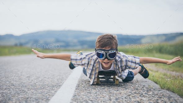 Happy little boy playing on the road at the day time. - Stock Photo - Images