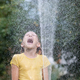 Happy little girl pouring water from a hose. - PhotoDune Item for Sale