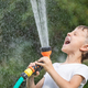 Happy little boy pouring water from a hose. - PhotoDune Item for Sale