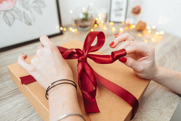 Woman wrapping present in paper with red ribbon. - Stock Photo - Images