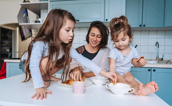 Mom and two daughters eat pancakes - Stock Photo - Images