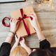 Woman wrapping present in paper with red ribbon. - PhotoDune Item for Sale