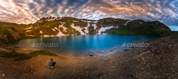 Backpacker Girl sits by the Lake Como Colorado USA - Stock Photo - Images