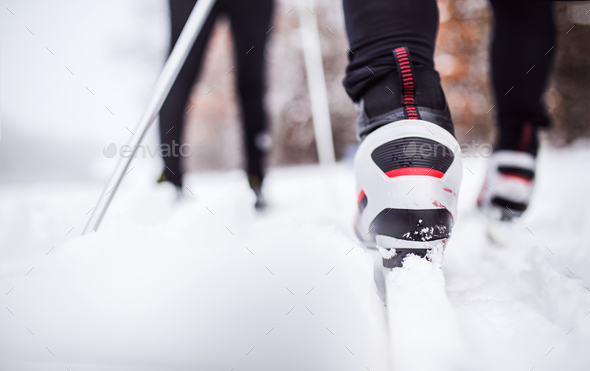 An unrecognizable couple cross-country skiing in winter. - Stock Photo - Images