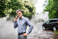 Mature man making a phone call after a car accident, smoke in the background. - PhotoDune Item for Sale