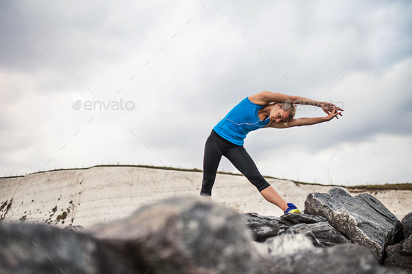 Young sporty woman runner with earphones standing on the rocks outside, stretching. - Stock Photo - Images