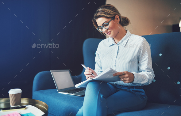 Smiling young businesswoman sitting on a sofa reading documents - Stock Photo - Images