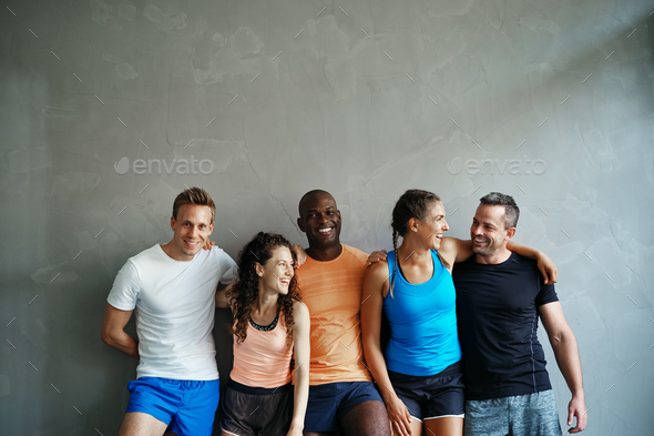 Diverse group of laughing friends standing together at the gym - Stock Photo - Images