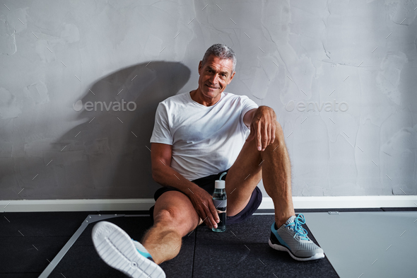 Smiling mature man taking a break after working out - Stock Photo - Images