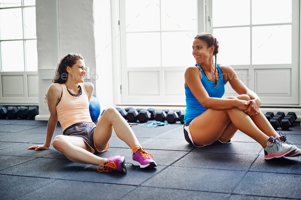 Two smiling female friends talking together on a gym floor - Stock Photo - Images