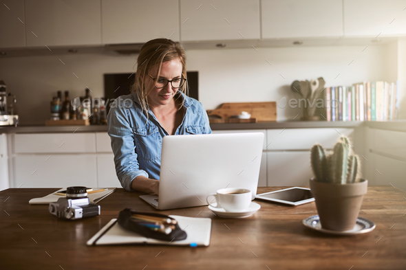 Female entrepreneur sitting in her kitchen working on a laptop - Stock Photo - Images