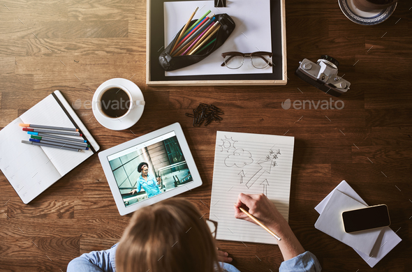 Designer sketching in a notepad while working from home - Stock Photo - Images