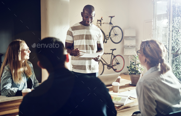 Smiling young African man giving a presentation to office colleagues - Stock Photo - Images