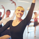 Smiling Mature ballet dancer exercising in ballet class - PhotoDune Item for Sale
