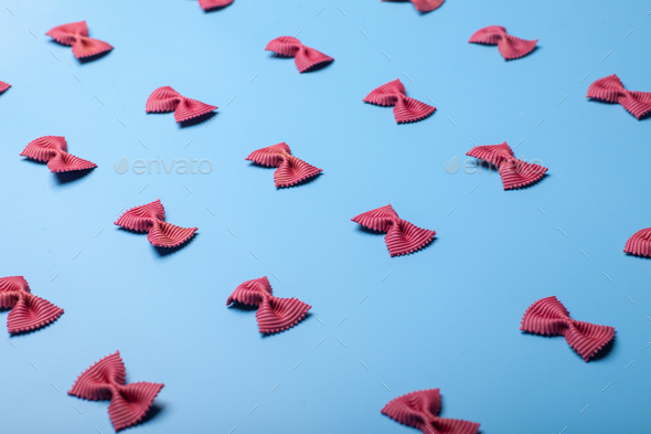 purple pasta farfalle on blue background - Stock Photo - Images