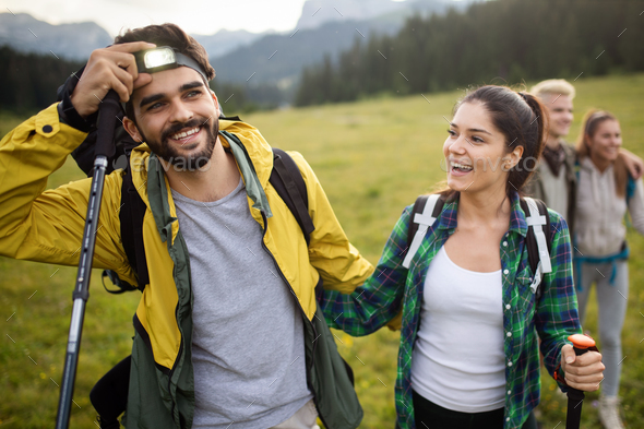 Backpackers happy young couple hiking with sticks - Stock Photo - Images