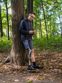 Young man with prosthetic leg using his smartphone - PhotoDune Item for Sale