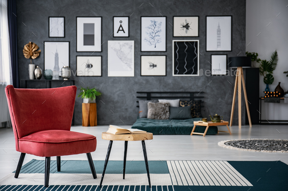 Red Armchair Next To Table On Carpet In Dark Grey Living Room