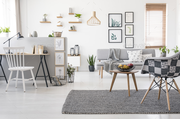 Checkered, stylish chair on a gray rug in a spacious, scandinavi - Stock Photo - Images